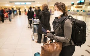 woman in airport pandemic travel